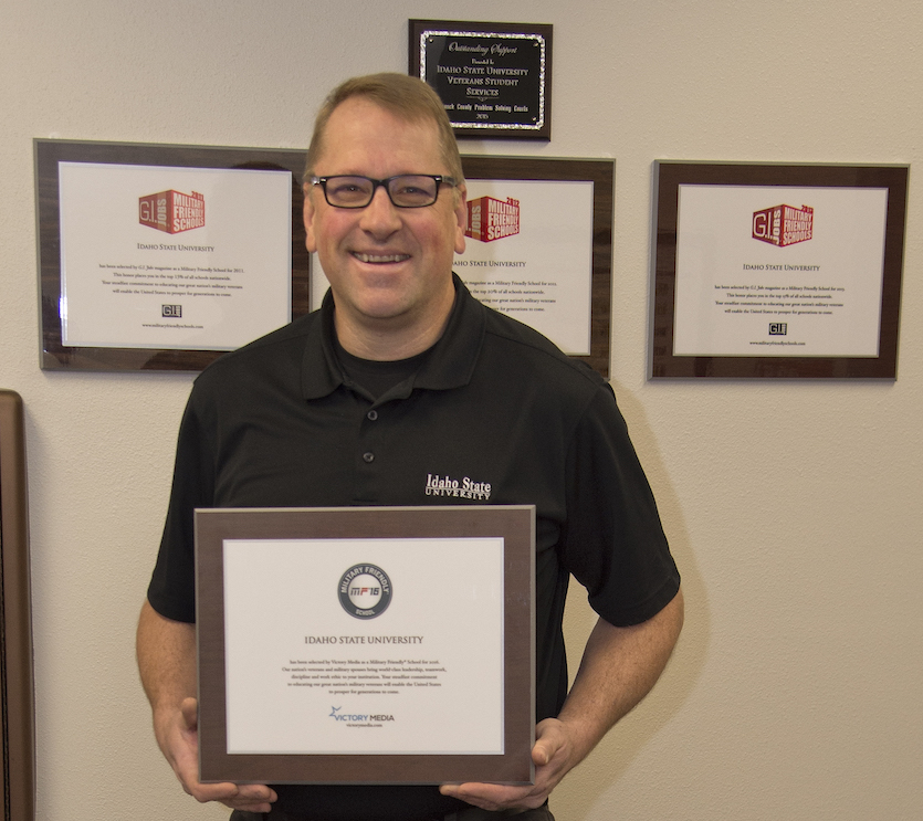 Veteran Student Services Center's Todd Johnson, displaying awards the center has received for 2018.