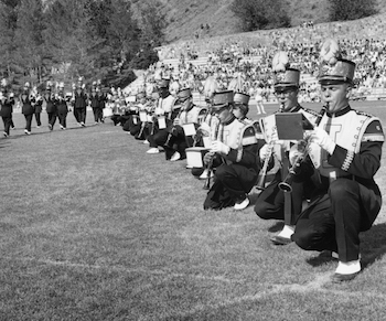 marching band members kneeling on the field at the Spud Bowl.