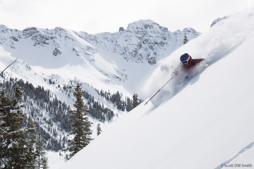 Photo of Pocatello's Ty Peterson skiing through powder snow way up on a mountain ridge.