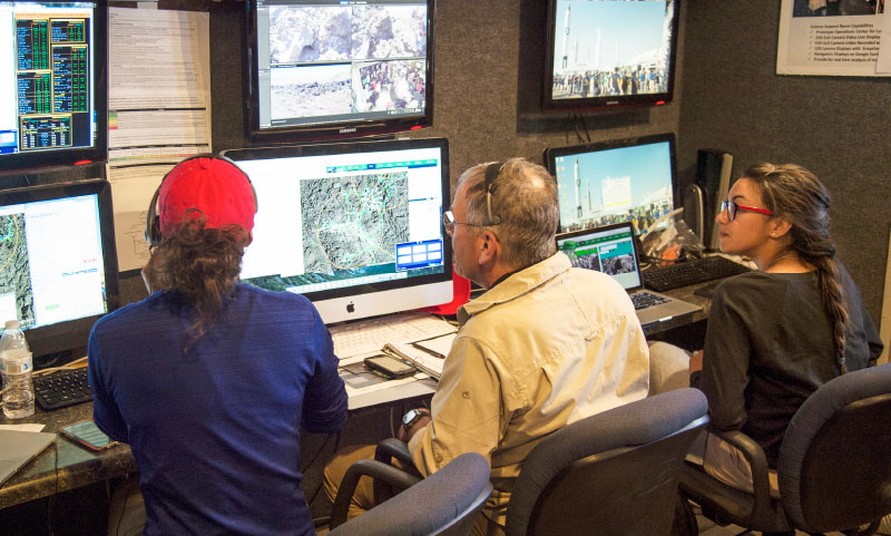 NASA's Kara Beaton and Rick Elphic, and participating high school student Chanel Vidal monitor computer screens in NASA's Mobile Mission Control Center that was set up in Arco this summer