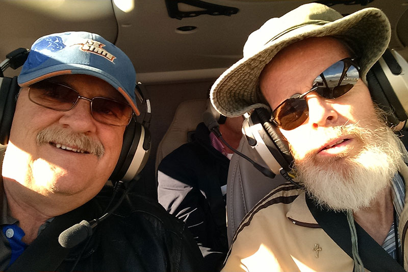 Steve and Bill Smylie in a helicopter cockpit on one of their adventures in recent years